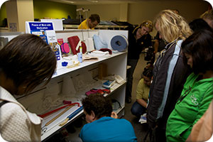tour participants looking at a shelf of assistive technology