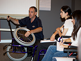 trainer demonstrating features of a wheelchair