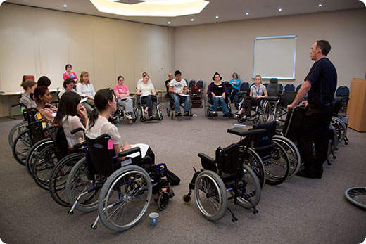 class organised in a circle of wheelchairs listening to instructor