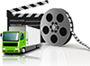 small green truck sitting in front of giant movie reel